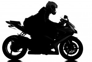 Silhouette of a motorcycle racer with helmet on the white background.